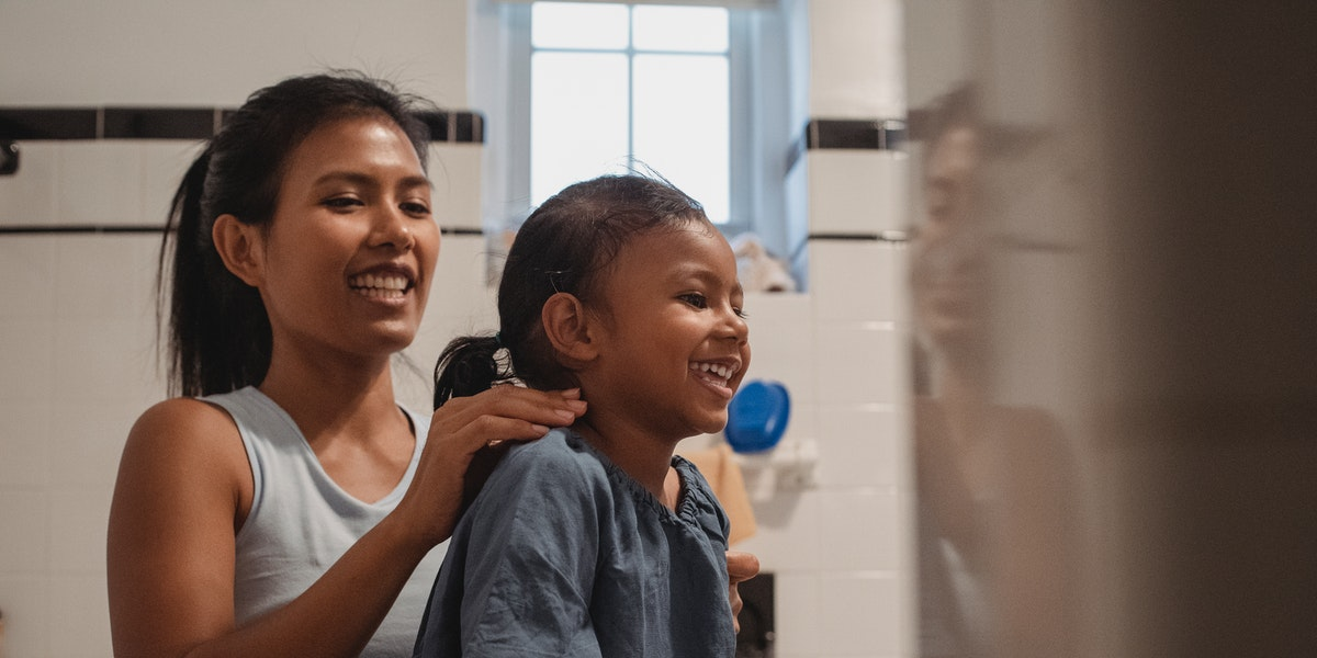 mom brushing child's hair looking for lice